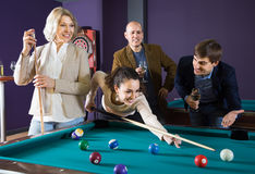 Happy middle class people playing pool game in billiard club Stock Images