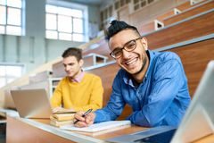 Happy Middle-Eastern Man in College. Portrait of two students sitting at desks in modern auditorium at college and preparing for class, focus on young Middle stock photo