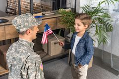 Happy military father and son with usa flag. At home royalty free stock images