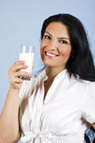 Happy milk woman. Beautiful happy young woman holding a full glass with milk and smiling you,concept of healthy lifestyle,on blue background,check also my Royalty Free Stock Photos