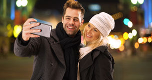 Happy millenial couple having fun taking selfies together at night in the city.  Stock Photo
