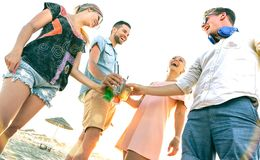 Happy millenial friends group having fun at beach party drinking fancy cocktails at sunset - Summer joy and friendship concept royalty free stock photos