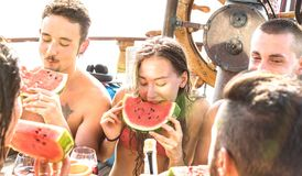 Happy millenial friends having fun at sail boat party with watermelon sangria and champagne - Cool friendship concept stock photo