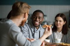 Happy african man laughing at friends joke hanging in pizzeria. Happy millennial african american men laughing at joke hanging in pizzeria sharing pizza with Royalty Free Stock Photos