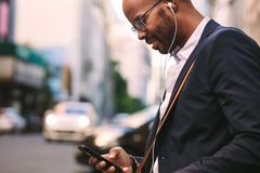 Businessman commuting with a smartphone on city street royalty free stock images