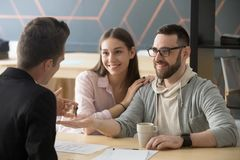 Happy millennial couple getting keys to new home from realtor. Customers renters tenants make deal buying renting house at meeting with agent, mortgage loan stock photo