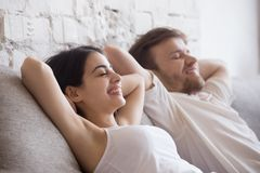 Happy couple lying relaxing on sofa with eyes closed royalty free stock image