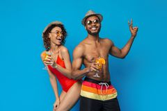 Happy millennial couple in swimwear drinking summer cocktails stock photo