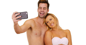 Happy millennial couple taking pictures with smartphone at the beach Royalty Free Stock Images