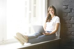 Happy millennial girl w/ laptop on windowsill. Portrait of young woman with diastema gap between teeth. Beautiful smile. Minimal i royalty free stock photography