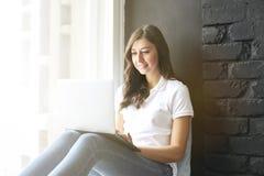 Happy millennial girl w/ laptop on windowsill. Portrait of young woman with diastema gap between teeth. Beautiful smile. Minimal i stock photos