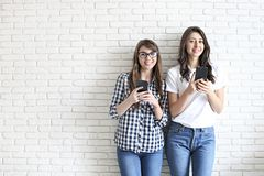 Happy millennial girls having fun indoors. Young beautiful women with perfect charismatic smiles, brown eyes, wavy dark hair. Mini stock photos