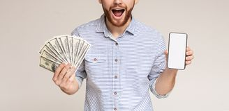 Happy millennial man with dollars and phone with blank space royalty free stock photos
