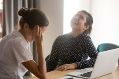 Smiling women have fun laughing at break at workplace. Happy millennial multiethnic women have fun sitting at office desk talking, smiling diverse female stock photo