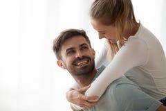 Happy millennial wife piggyback smiling husband having fun at ho stock image