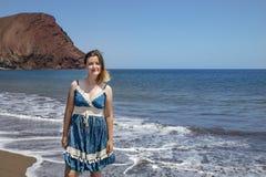 Happy millennial woman wearing a blue paisley dress while enjoying a beautiful day on La Tejita beach, Tenerife, Canary Islands