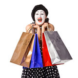 Happy mime in spotty dress holding shopping bags Royalty Free Stock Image