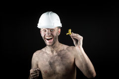 Happy  miner shows a golden nugget Royalty Free Stock Photography