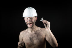 Happy  miner shows a silver nugget Royalty Free Stock Photo