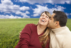 Happy Mixed Couple Sitting in Grass Field Royalty Free Stock Images