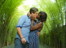 Happy mixed ethnicity couple kissing outdoors with attractive black African American woman and handsome Caucasian boyfriend or. Young attractive and happy mixed royalty free stock image