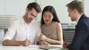 Happy mixed ethnicity couple make deal sign contract handshake insurer
