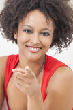 Happy Mixed Race African American Girl Pointing. A beautiful mixed race African American girl or young woman wearing a red dress looking happy and pointing to Stock Photos