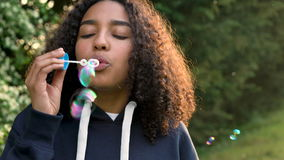 Happy mixed race African American girl teenager or young woman laughing, smiling and blowing bubbles at sunset or sunrise stock footage
