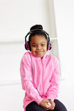 Happy girl listens to music. A happy mixed race African American - Hispanic heritage girl smiles while listening to her favorite music Stock Image