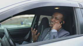 Happy mixed race businessman talking phone while sitting inside his car outdoors stock video footage