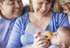 Happy Mixed Race Couple Bottle Feeding Thier Son Royalty Free Stock Photography