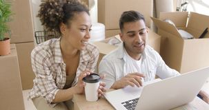 Happy mixed race couple discuss while using laptop stock video