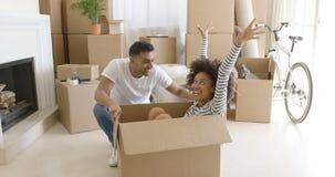 Happy mixed race couple having fun break with unpacking Stock Image