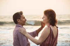 Happy mixed race couple near beach at sunset. Royalty Free Stock Photography