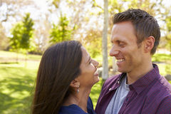 Happy mixed race couple in park look at each other, close up Royalty Free Stock Images