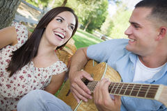 Happy Mixed Race Couple at the Park Playing Guitar and Singing Stock Photos