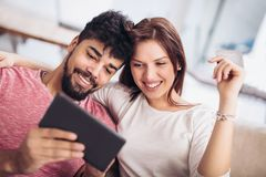 Happy mixed race couple shopping online at home. Using credit card, laughing royalty free stock photo