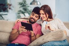 Happy mixed race couple shopping online at home, using credit card. Laughing stock photo