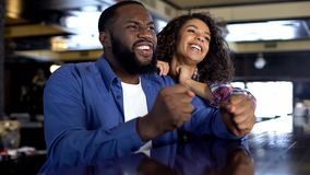 Happy mixed-race couple supporting national team watching game, entertainment. Stock photo stock photo