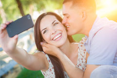 Happy Mixed Race Couple Taking Self Portrait with A Smart Phone Stock Photo