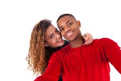Happy mixed race couple taking a selfie photo over a white backg Stock Photos