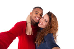 Happy mixed race couple taking a selfie photo over a white backg Royalty Free Stock Image