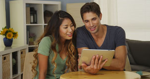 Happy mixed race couple talking on tablet royalty free stock photo