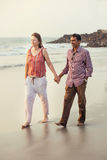 Happy mixed race couple walking on the beach Royalty Free Stock Photo