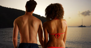 Happy mixed race couple watching sunset from beach. Happy mixed race couple watching sunset from beach Stock Photo