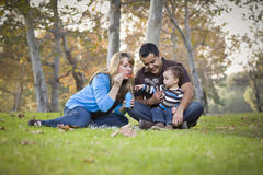 Happy Mixed Race Ethnic Family Playing with Bubbles In The Park. Happy Young Mixed Race Ethnic Family Playing Together with Bubbles In The Park royalty free stock photography