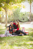 Happy Mixed Race Family Enjoying Christmas Gifts in the Park Stock Image