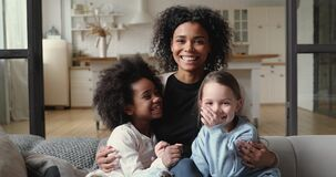 Happy mixed race family mother hugging diverse daughters at home