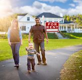 Happy Mixed Race Family in Front of Home and For Rent Sign. Happy Mixed Race Family Walking in Front of Home and For Rent Real Estate Sign stock photography