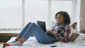 Happy mixed race girl having video chat with friends using laptop camera while lying on bed Royalty Free Stock Photo